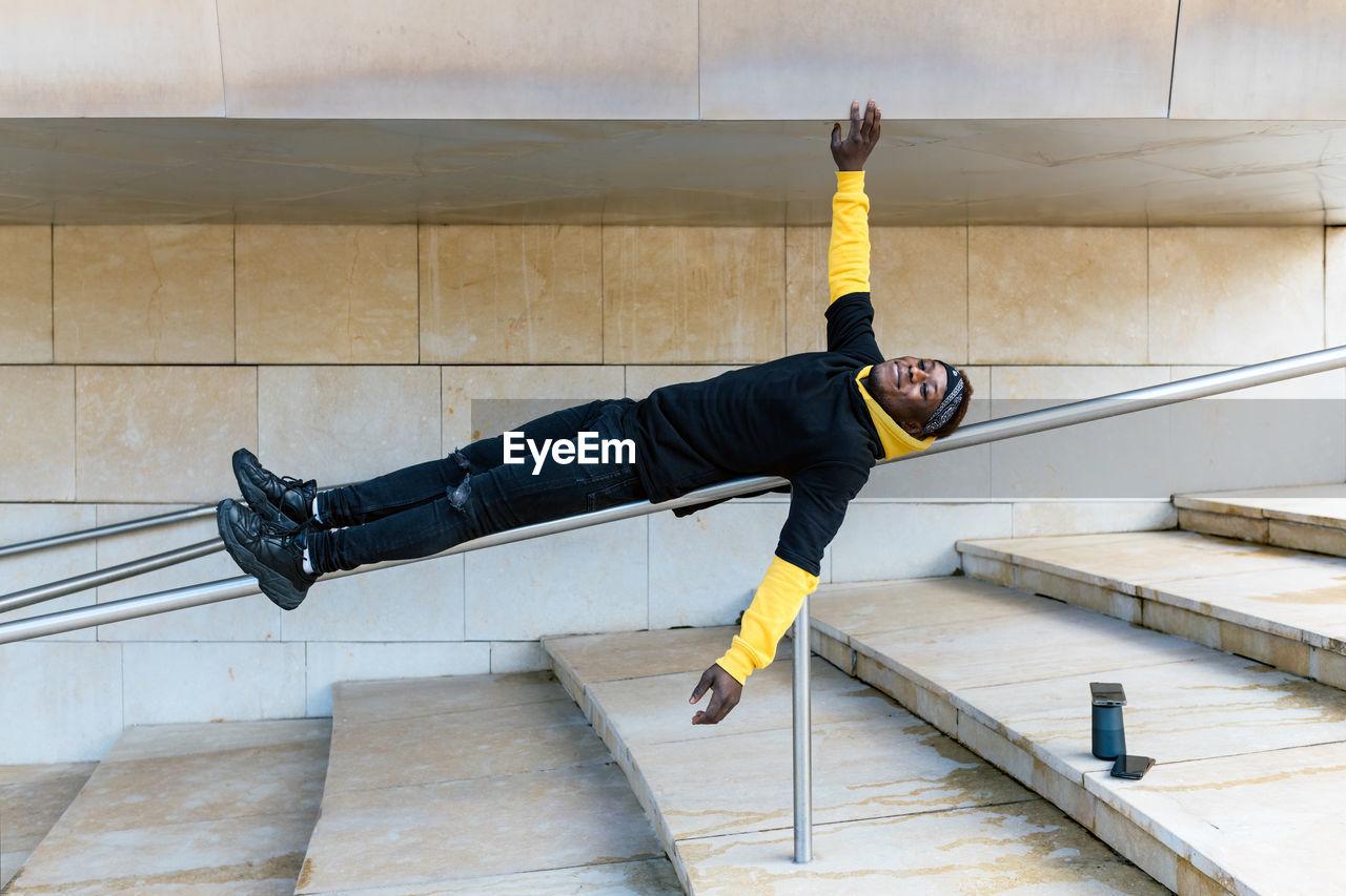 FULL LENGTH OF MAN SKATEBOARDING ON FLOOR AGAINST WALL