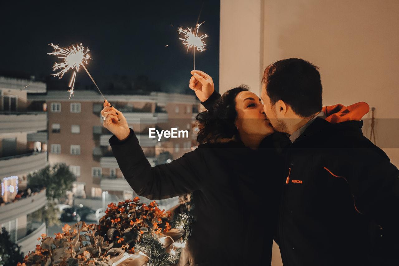 Couple holding illuminated sparklers while kissing