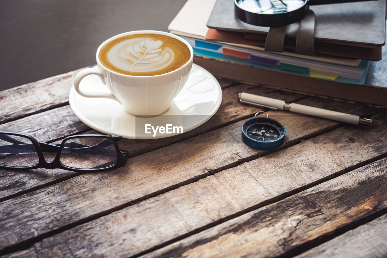 High angle view of coffee and books by eyeglasses on wooden table