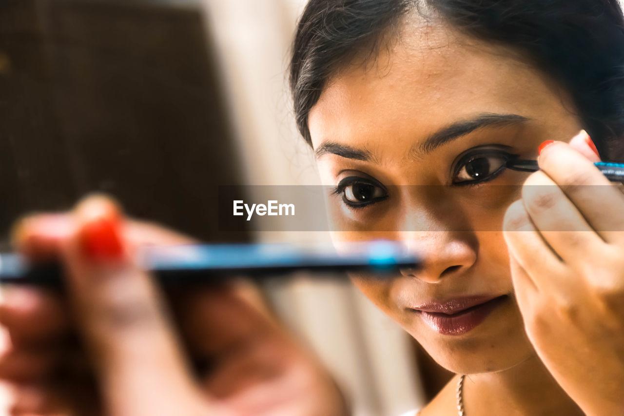 Close-up of woman applying eyeshadow