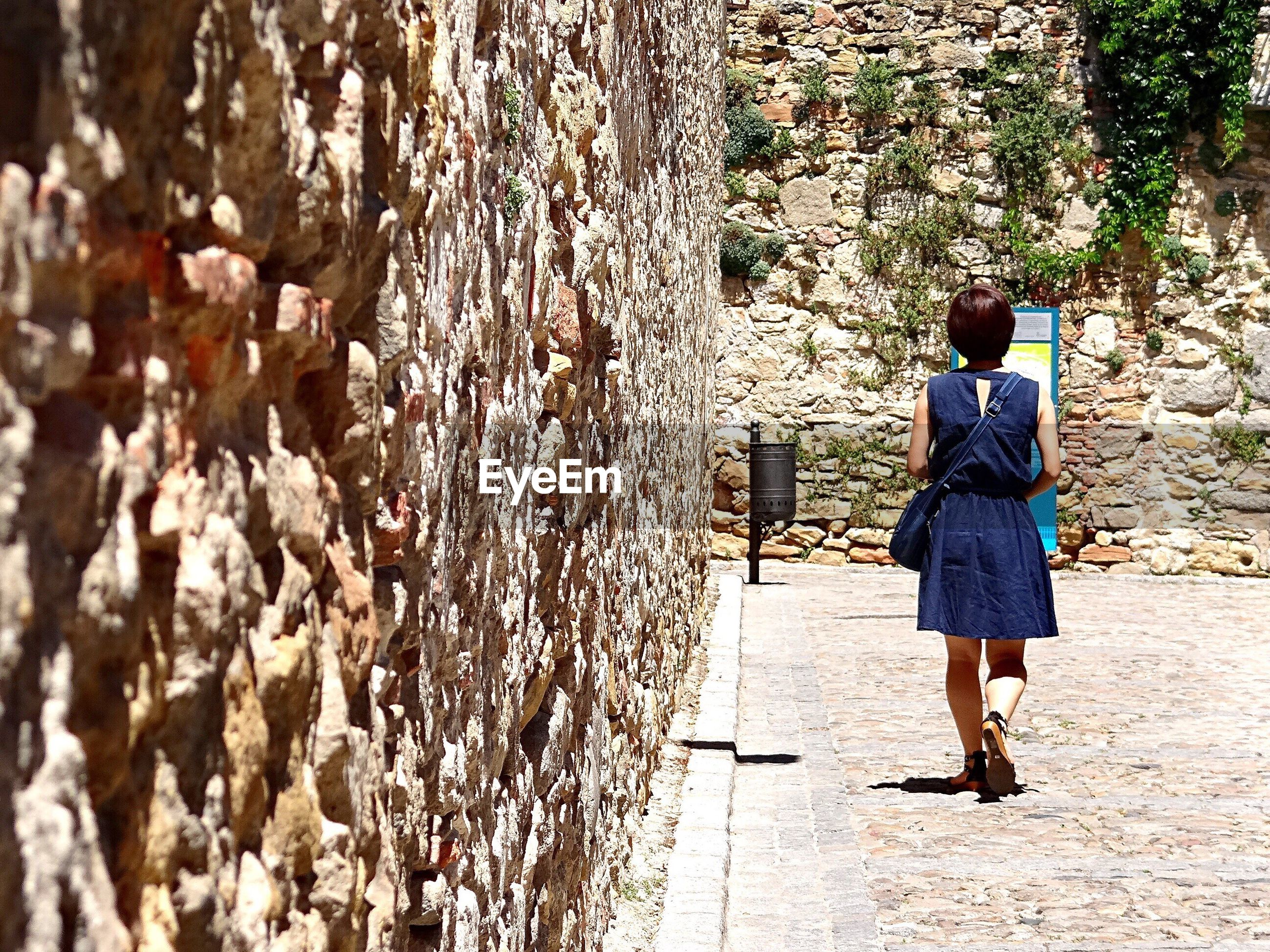 Full length rear view of woman walking by stone wall