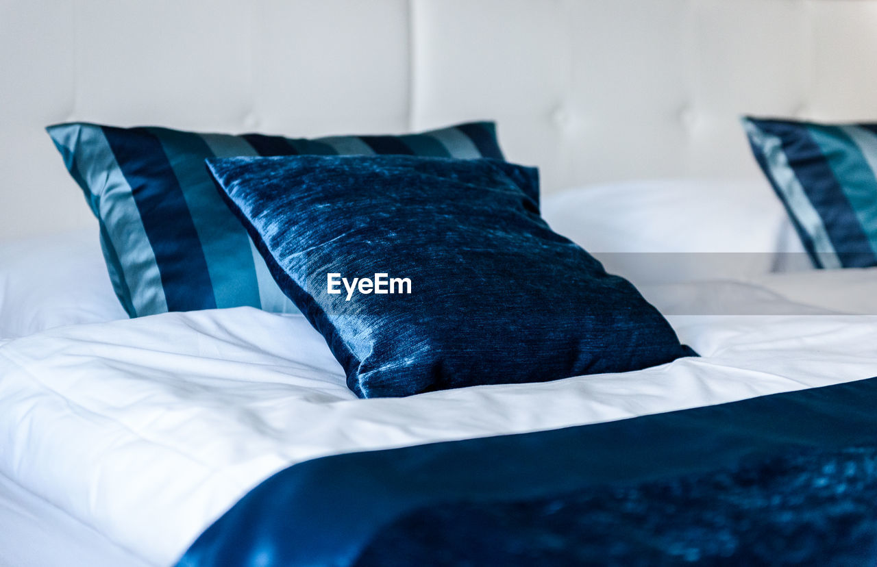 bed, pillow, furniture, indoors, bedroom, textile, blue, sheet, linen, no people, comfortable, white color, relaxation, domestic room, home interior, absence, cushion, stuffed, blanket, selective focus, duvet, cozy, softness, clean