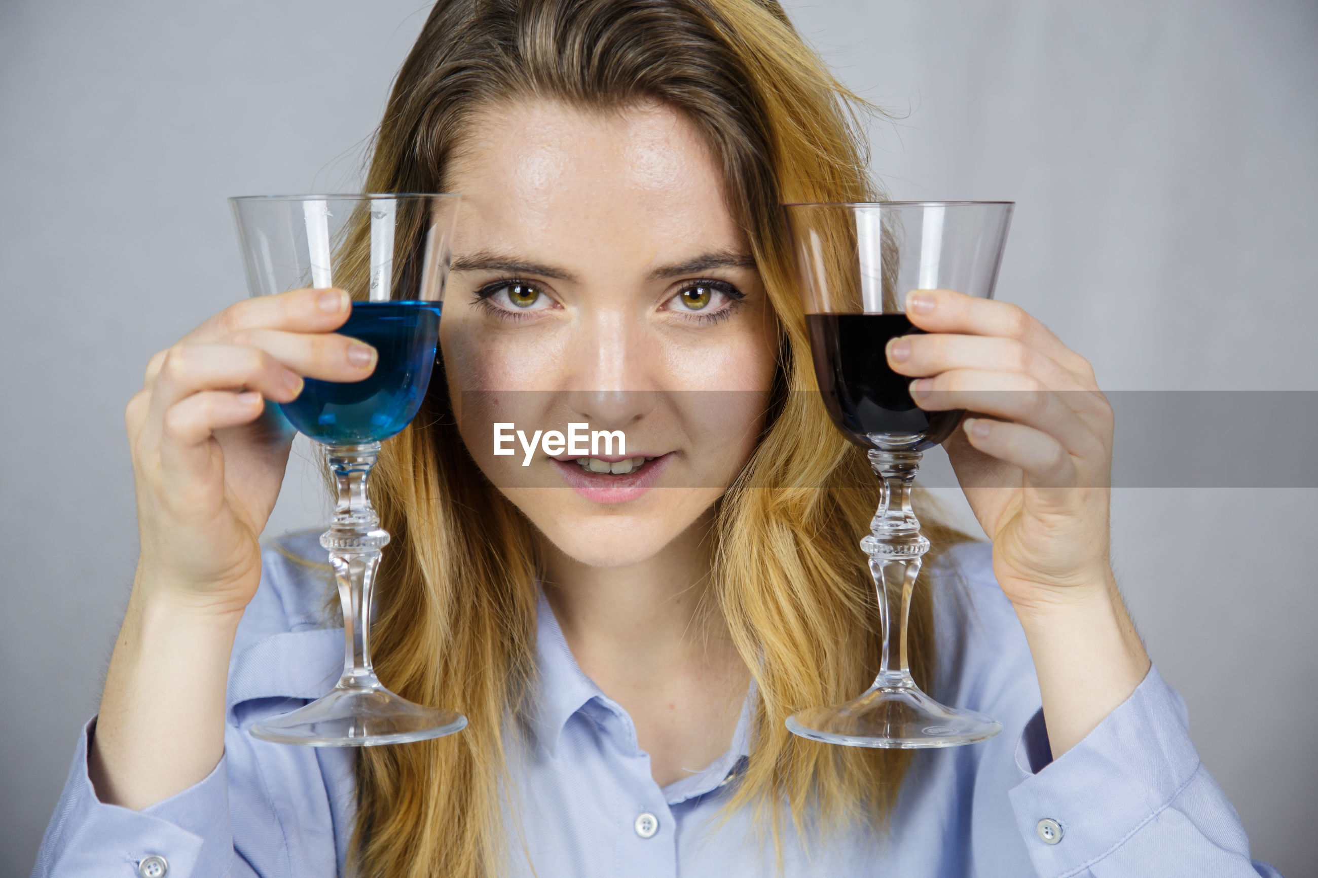 Portrait of young woman having drink in wineglasses against backdrop