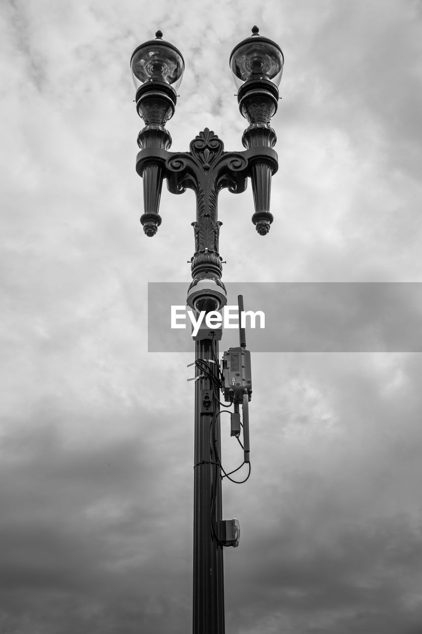cloud - sky, sky, low angle view, day, no people, nature, street light, technology, lighting equipment, pole, street, outdoors, metal, communication, tall - high, built structure, overcast, connection, architecture, power supply, electrical equipment