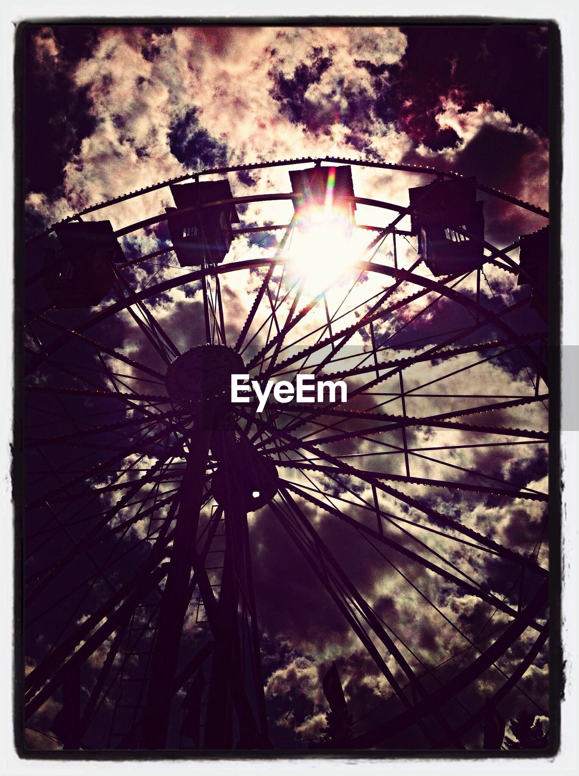 Low angle view of silhouette ferris wheel against cloudy sky