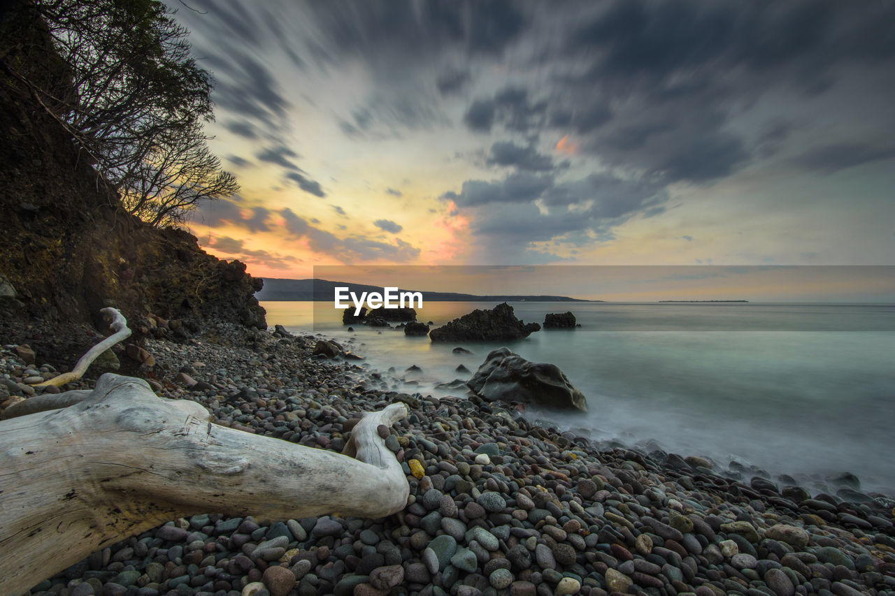 sky, water, sunset, cloud - sky, rock, scenics - nature, sea, solid, beauty in nature, beach, tranquility, nature, tranquil scene, land, rock - object, stone, horizon over water, no people, non-urban scene, pebble, outdoors, driftwood