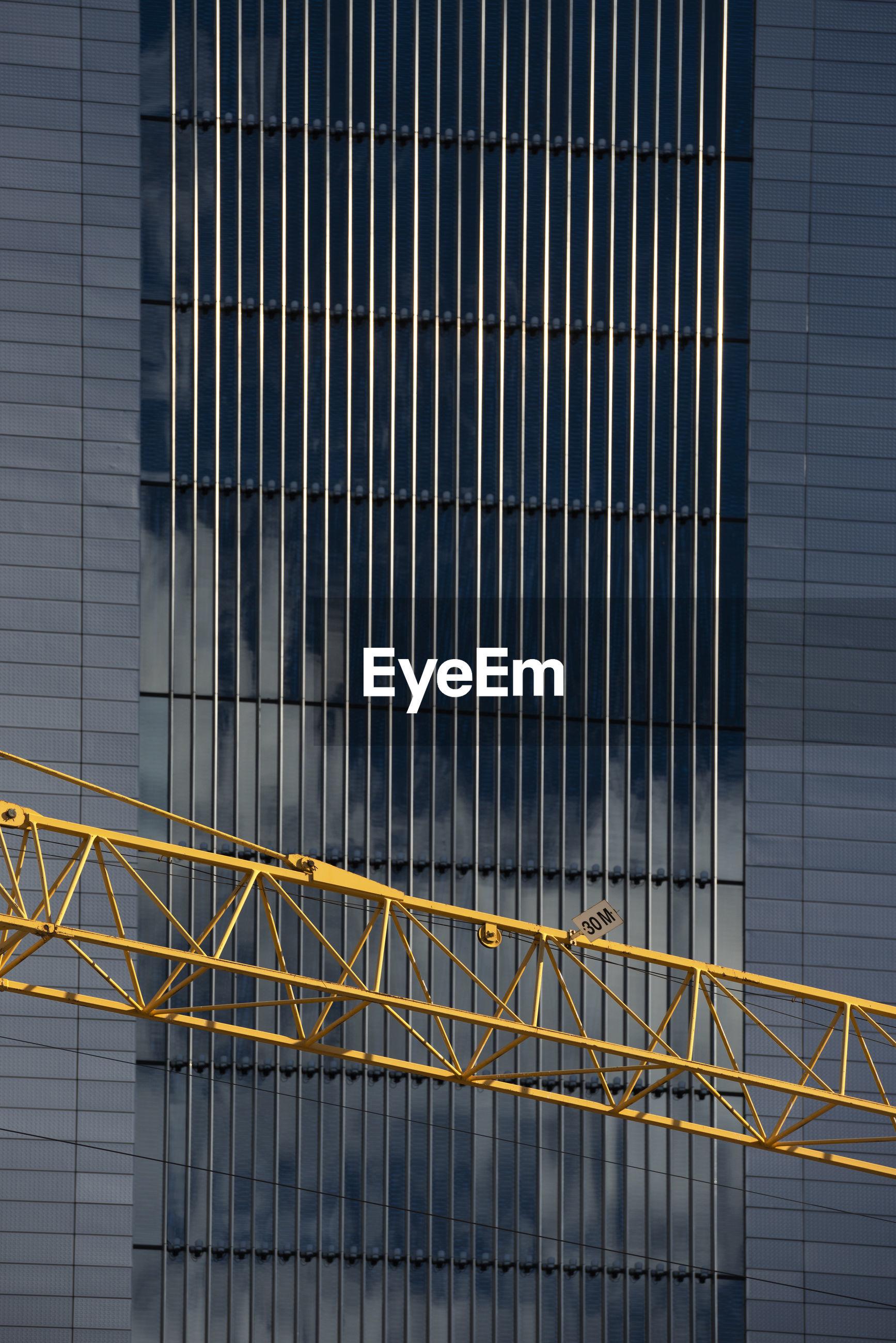 Metal railing of modern building and crane