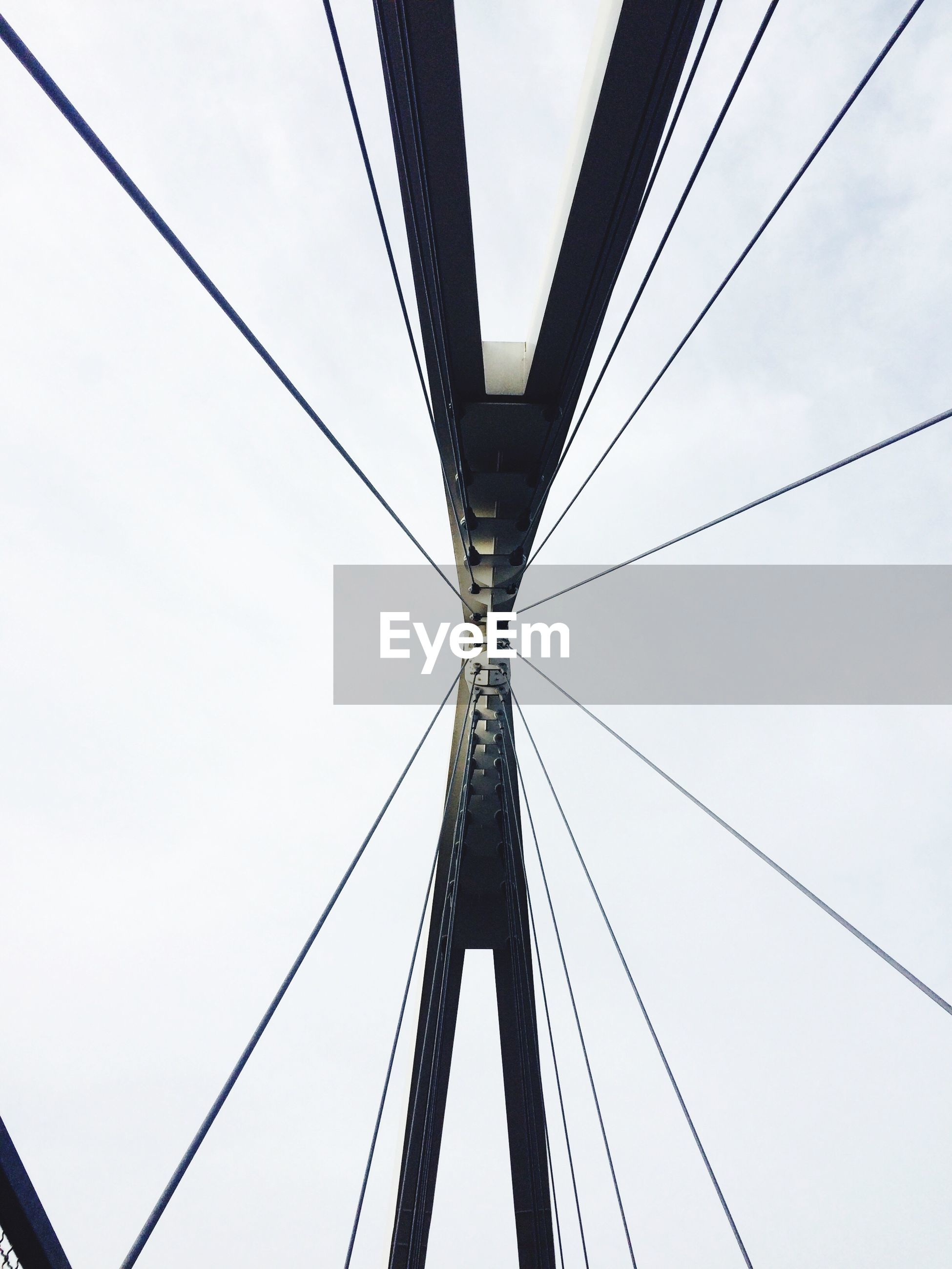 low angle view, connection, cable, power line, built structure, electricity pylon, architecture, engineering, clear sky, sky, power supply, electricity, day, no people, suspension bridge, outdoors, bridge - man made structure, metal, tall - high, part of