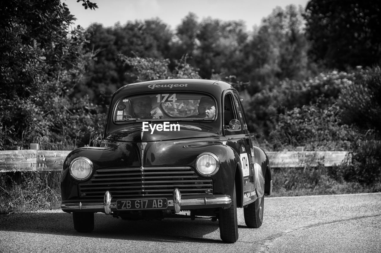 mode of transportation, transportation, car, motor vehicle, land vehicle, retro styled, tree, plant, day, vintage car, nature, old, road, no people, focus on foreground, field, metal, headlight, city