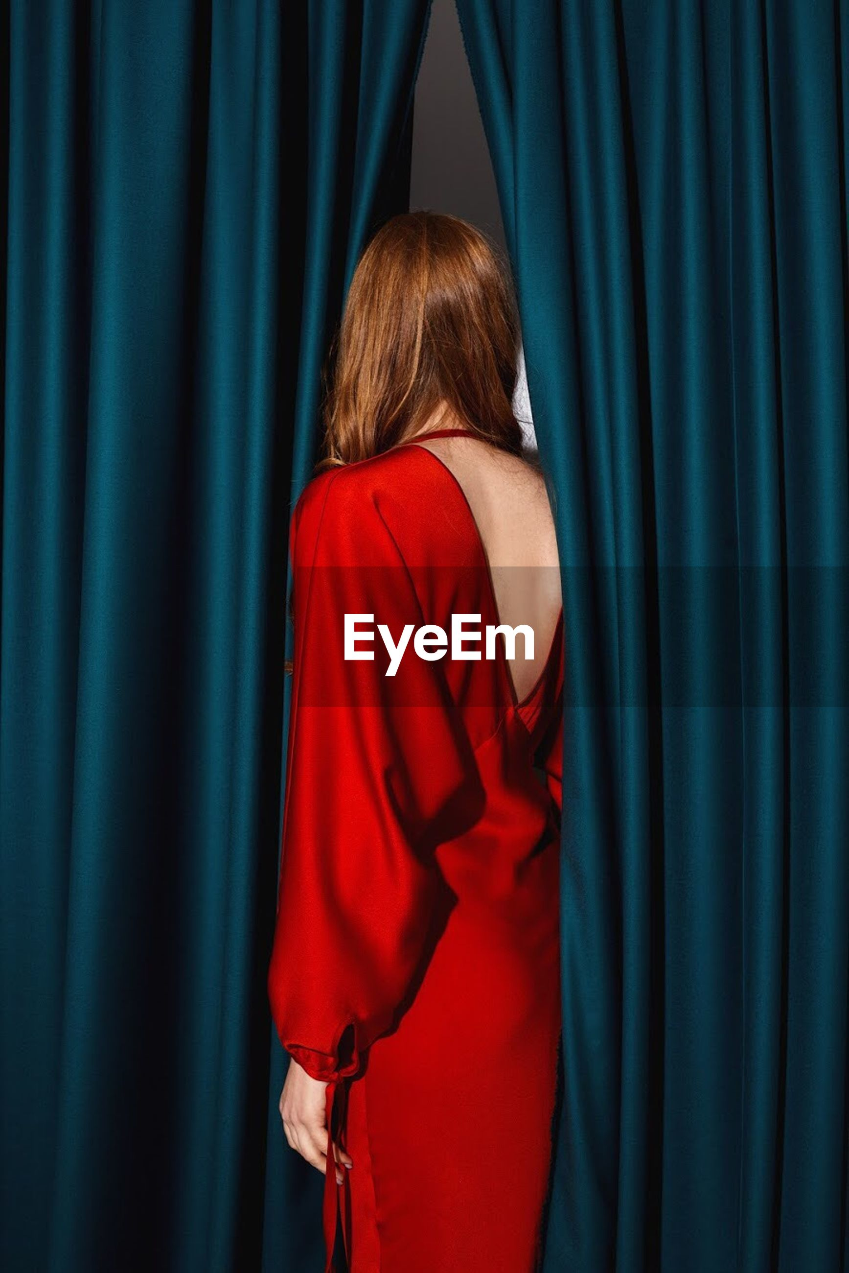 curtain, rear view, indoors, one person, stage, blue, adult, stage - performance space, women, red, standing, waist up, performance, peeking, hiding, casual clothing, arts culture and entertainment, textile, hairstyle
