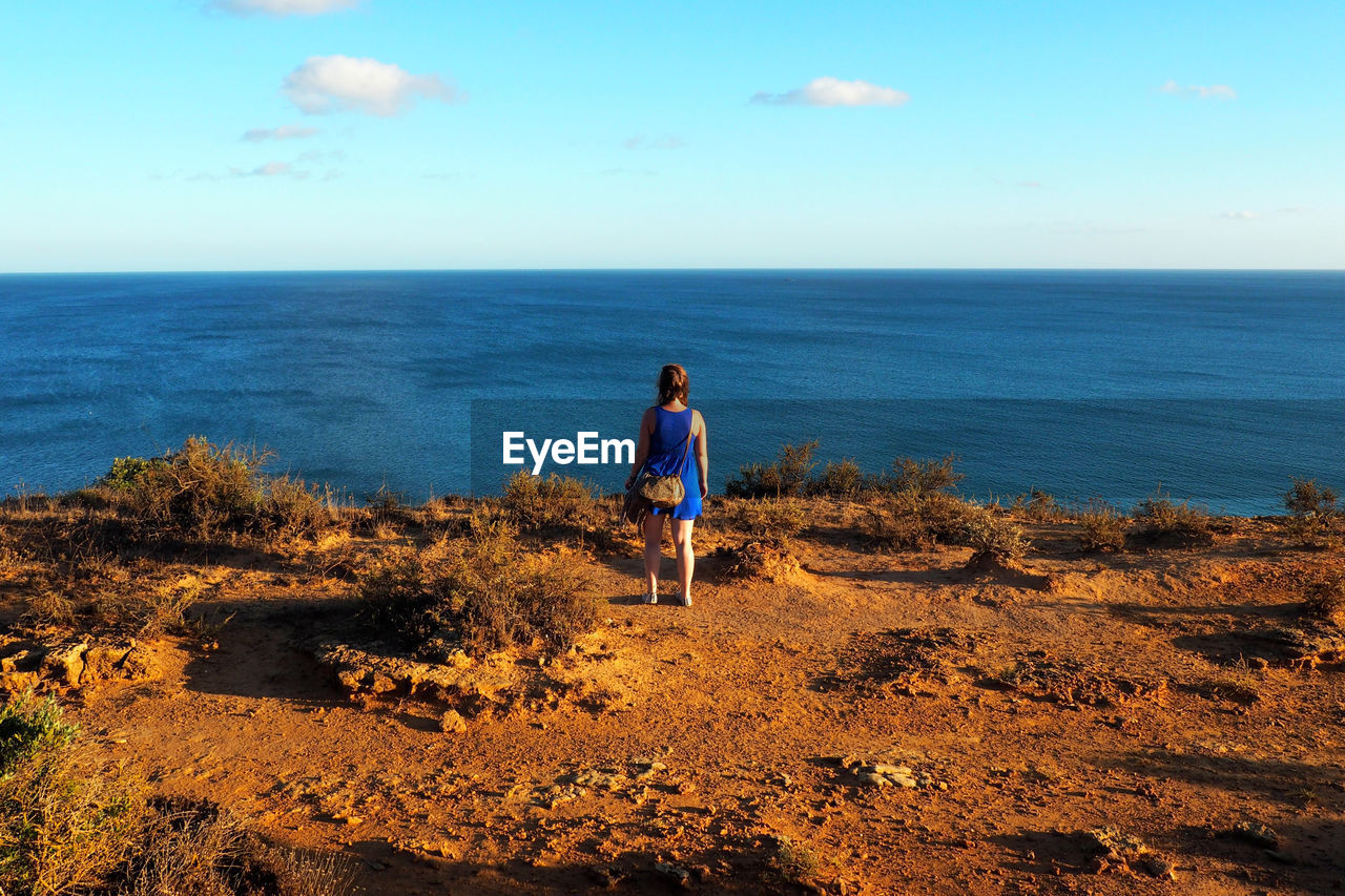 Rear View Full Length Of Woman Standing On Cliff Against Sea