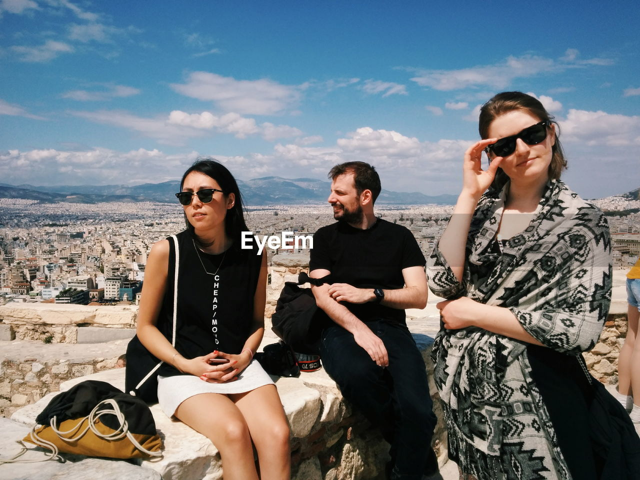 sky, young adult, using phone, telephone, leisure activity, glasses, lifestyles, real people, young men, sunglasses, three quarter length, technology, cloud - sky, front view, fashion, mobile phone, people, casual clothing, nature, wireless technology, outdoors
