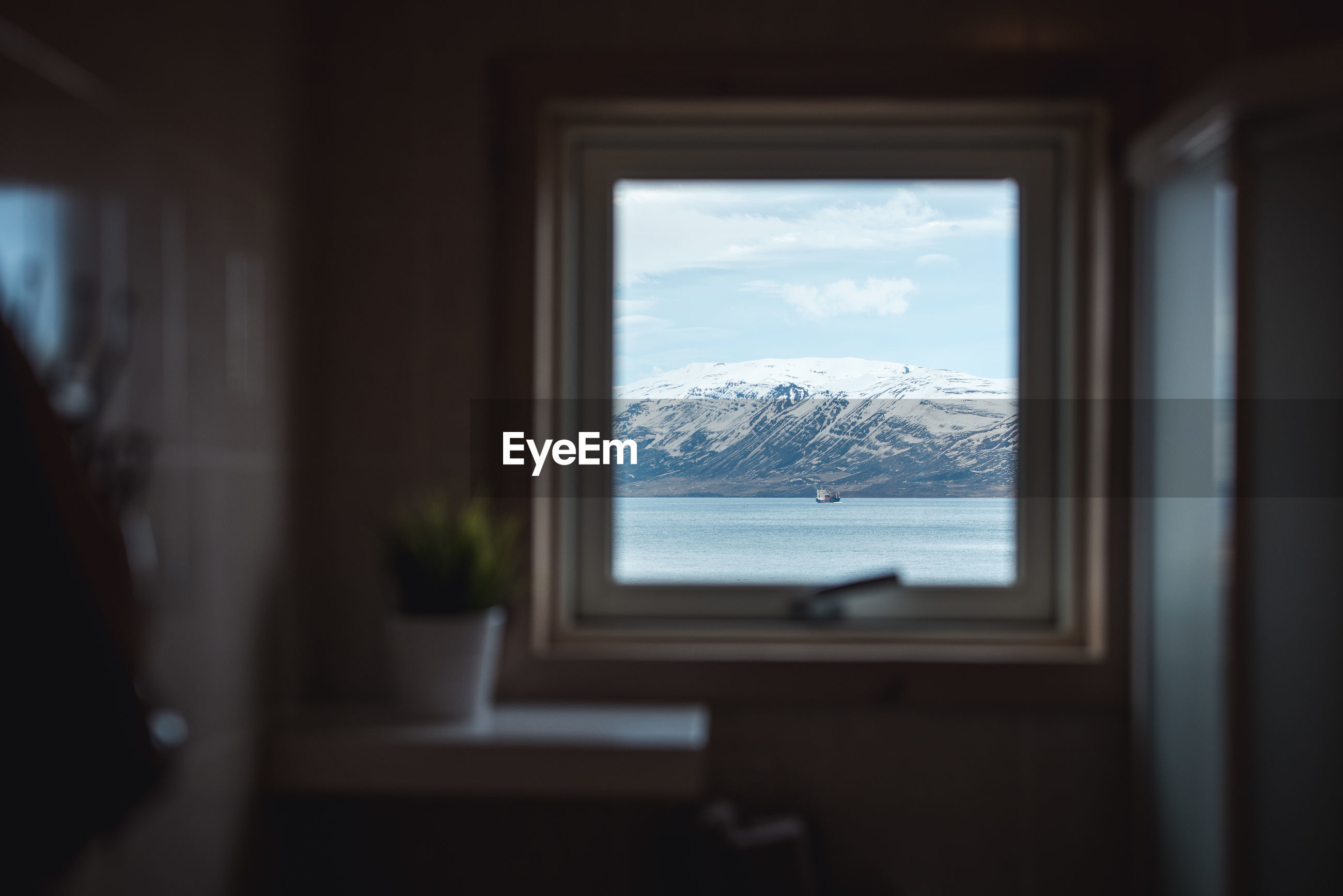 SNOW COVERED MOUNTAINS SEEN THROUGH WINDOW