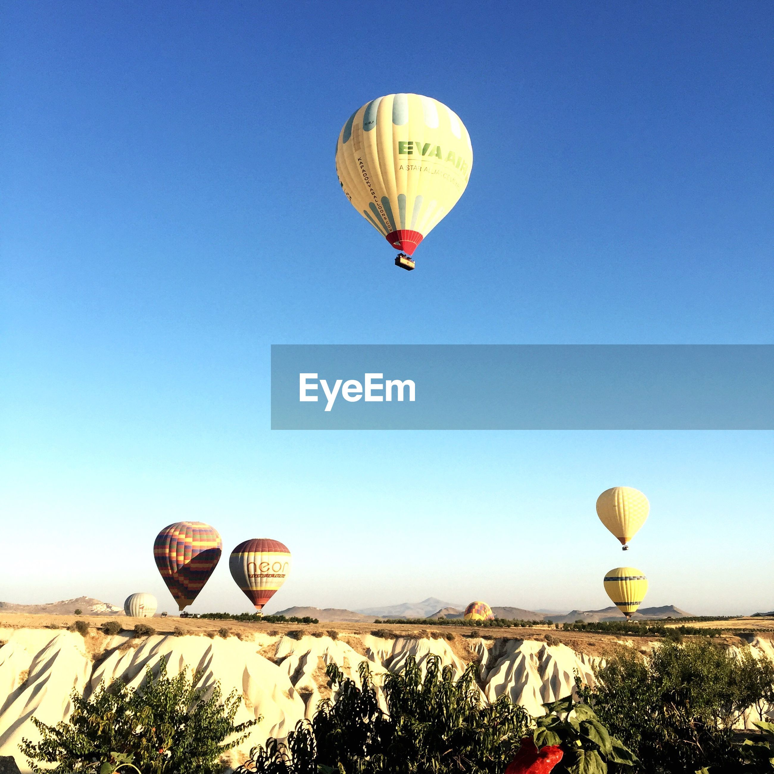 clear sky, transportation, mid-air, flying, hot air balloon, blue, air vehicle, outdoors, day, multi colored, nature, adventure, mountain, tranquility, scenics