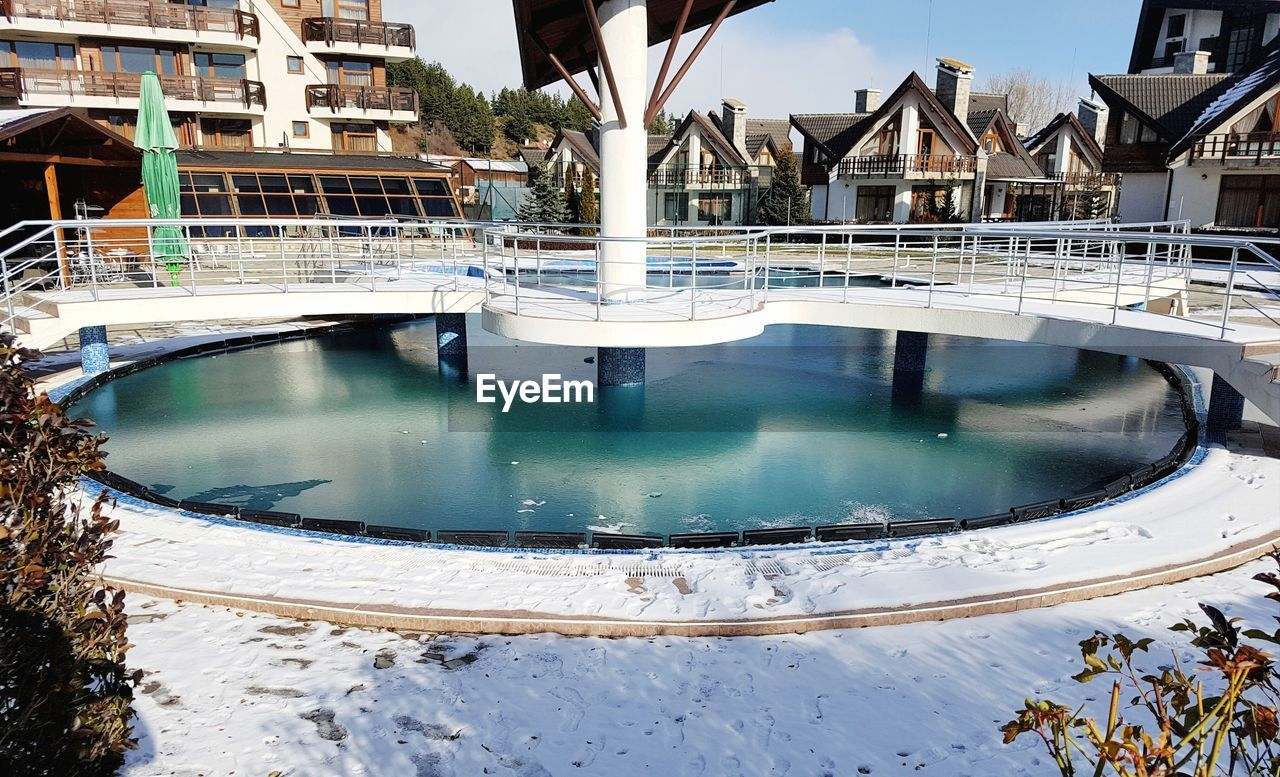 water, architecture, built structure, pool, building exterior, swimming pool, day, nature, no people, reflection, building, tourist resort, outdoors, travel destinations, sunlight, sky, residential district, poolside, cold temperature, luxury