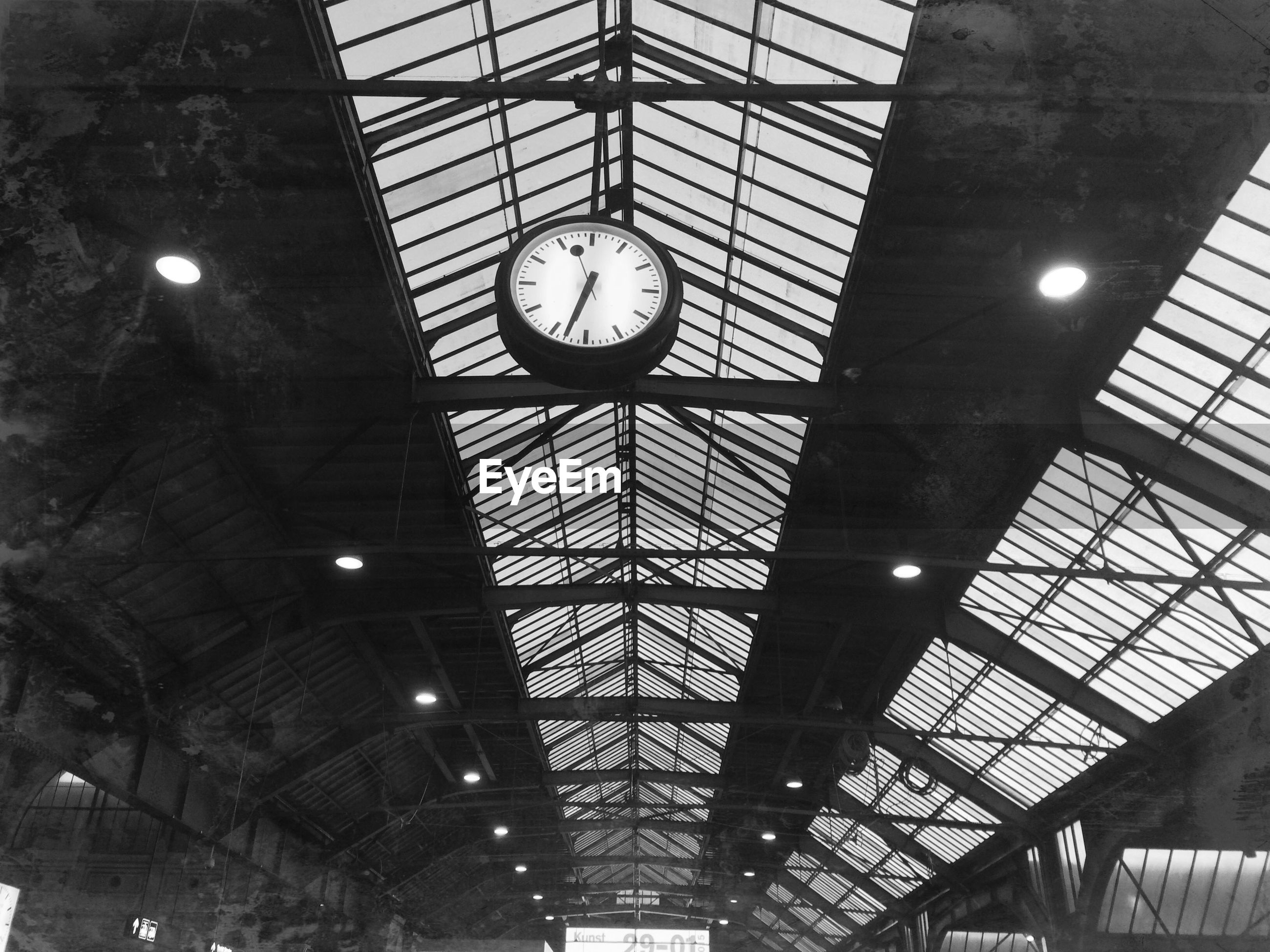 Low angle view of clock hanging from ceiling at railroad station