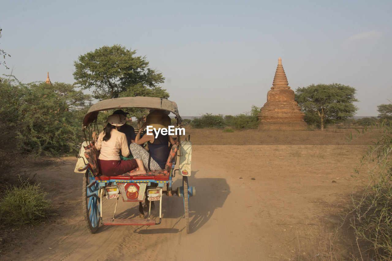 People traveling from cart on dirt road against temple