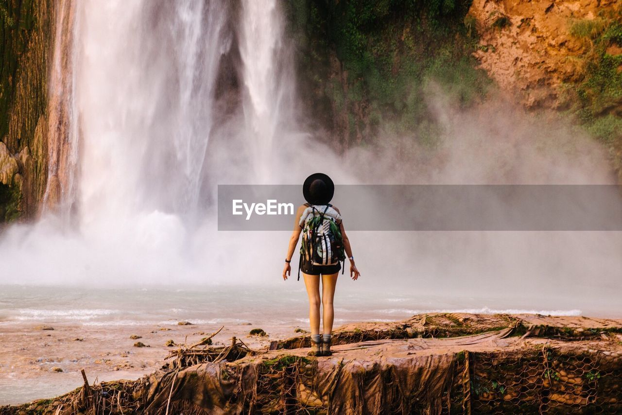 Full length rear view of woman standing against waterfall