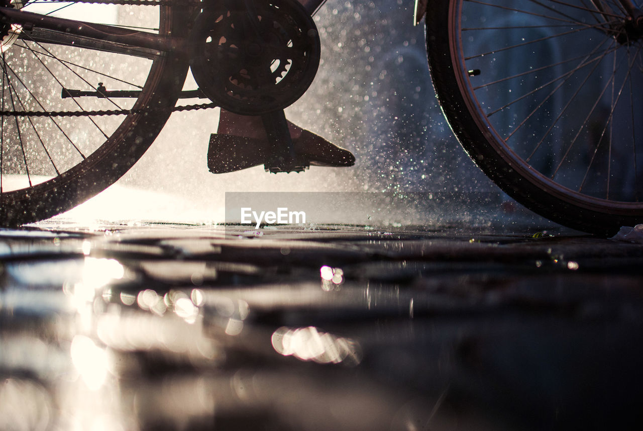 Low Section Of Person Cycling On Wet Footpath