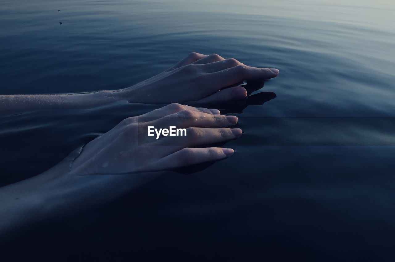 Cropped hand of woman in sea