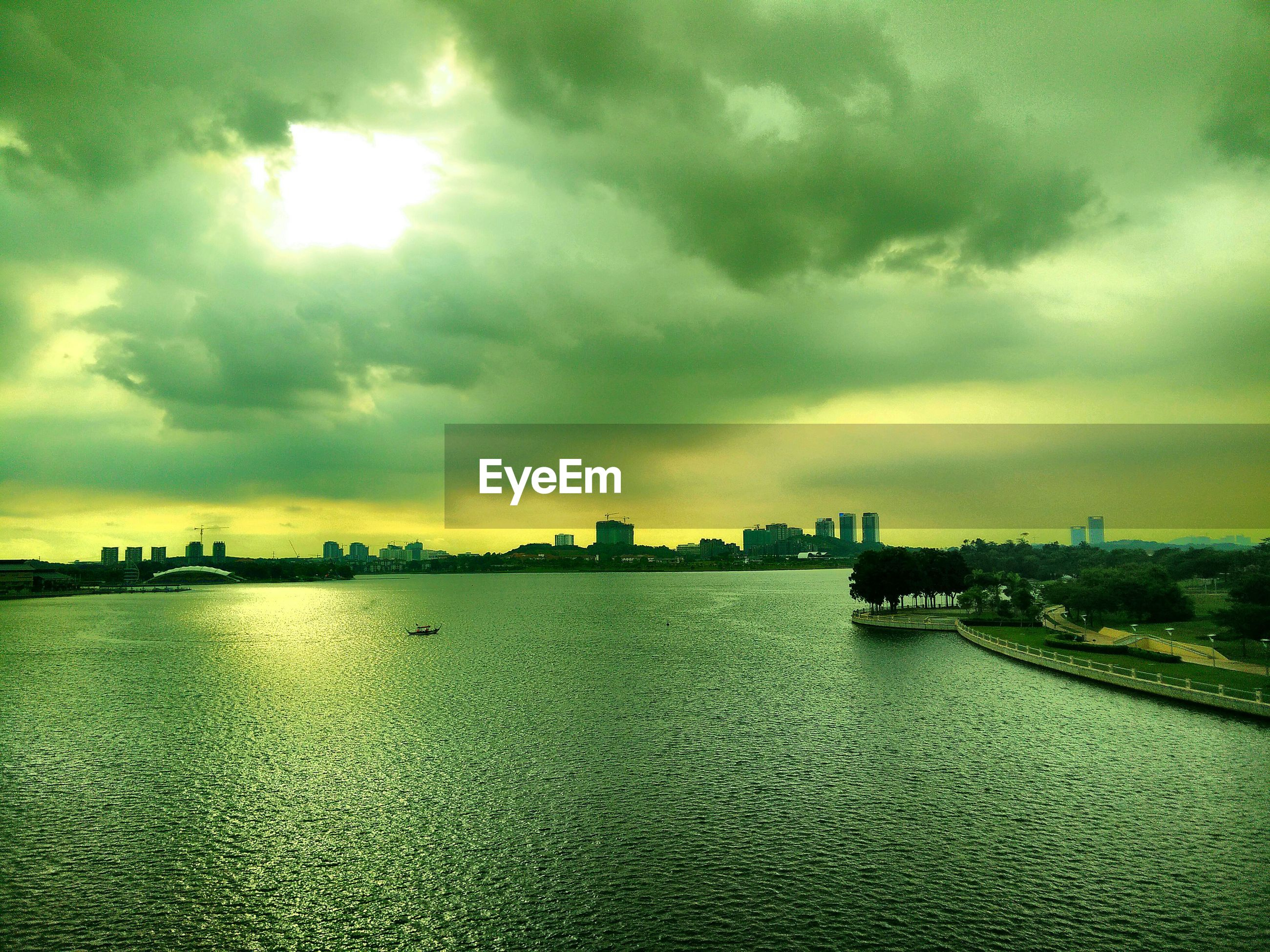 sky, water, cloud - sky, sea, cloudy, waterfront, building exterior, built structure, architecture, weather, sunset, overcast, city, scenics, cloud, dusk, storm cloud, dramatic sky, nature, tranquility
