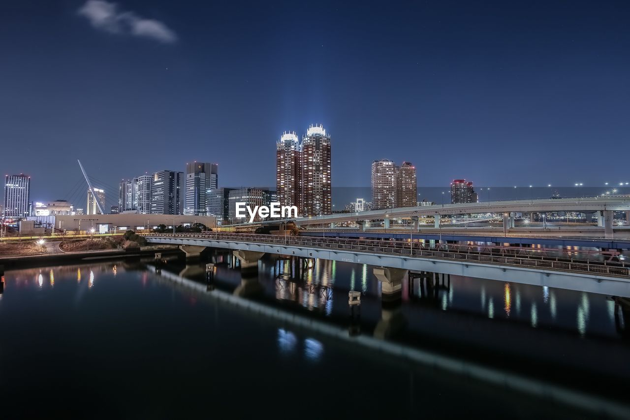 Bridge over river by illuminated buildings against sky at night
