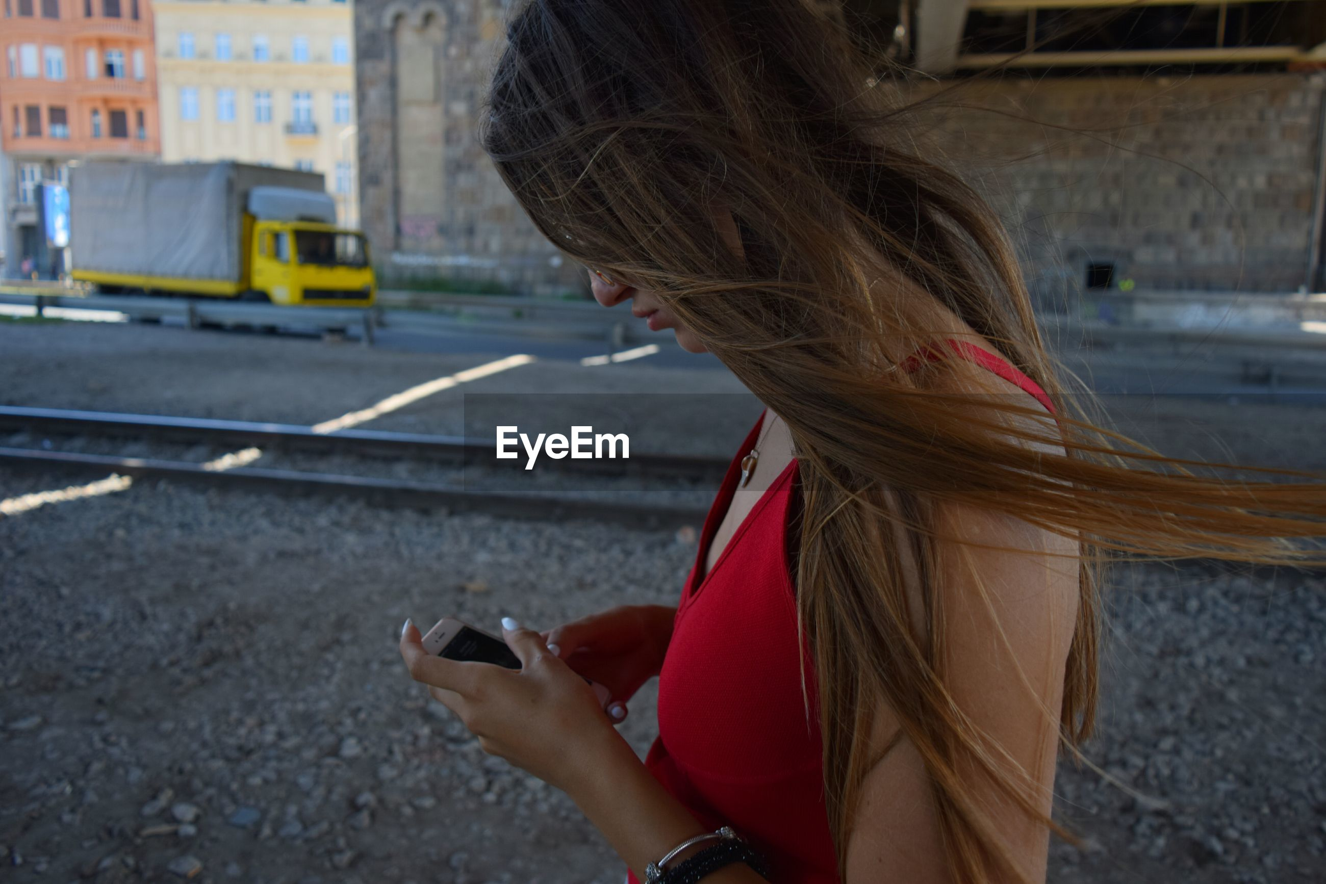 Side view of young woman using mobile phone while standing by railroad track