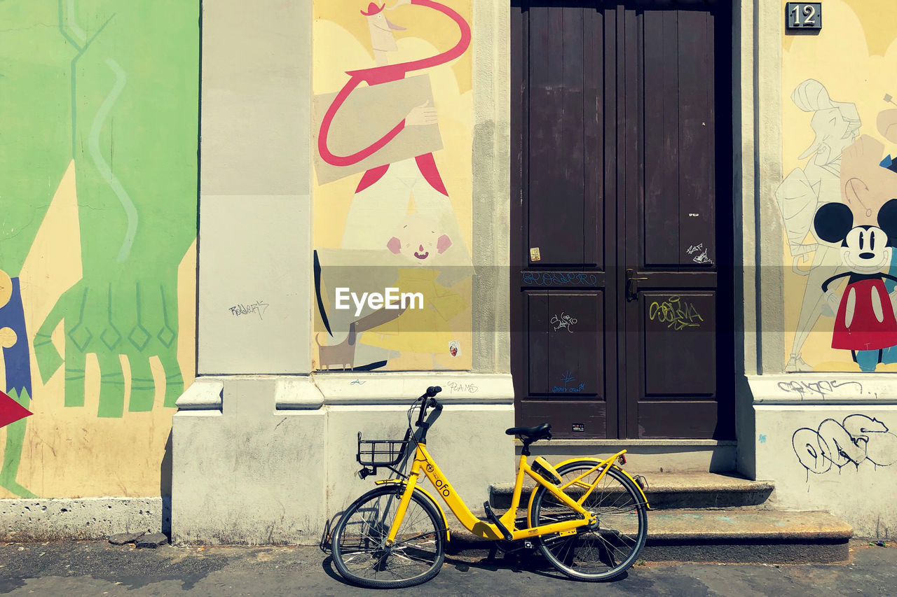 architecture, transportation, bicycle, land vehicle, mode of transportation, graffiti, built structure, no people, building exterior, creativity, wall - building feature, day, communication, art and craft, stationary, text, door, closed, entrance, yellow, outdoors, mural
