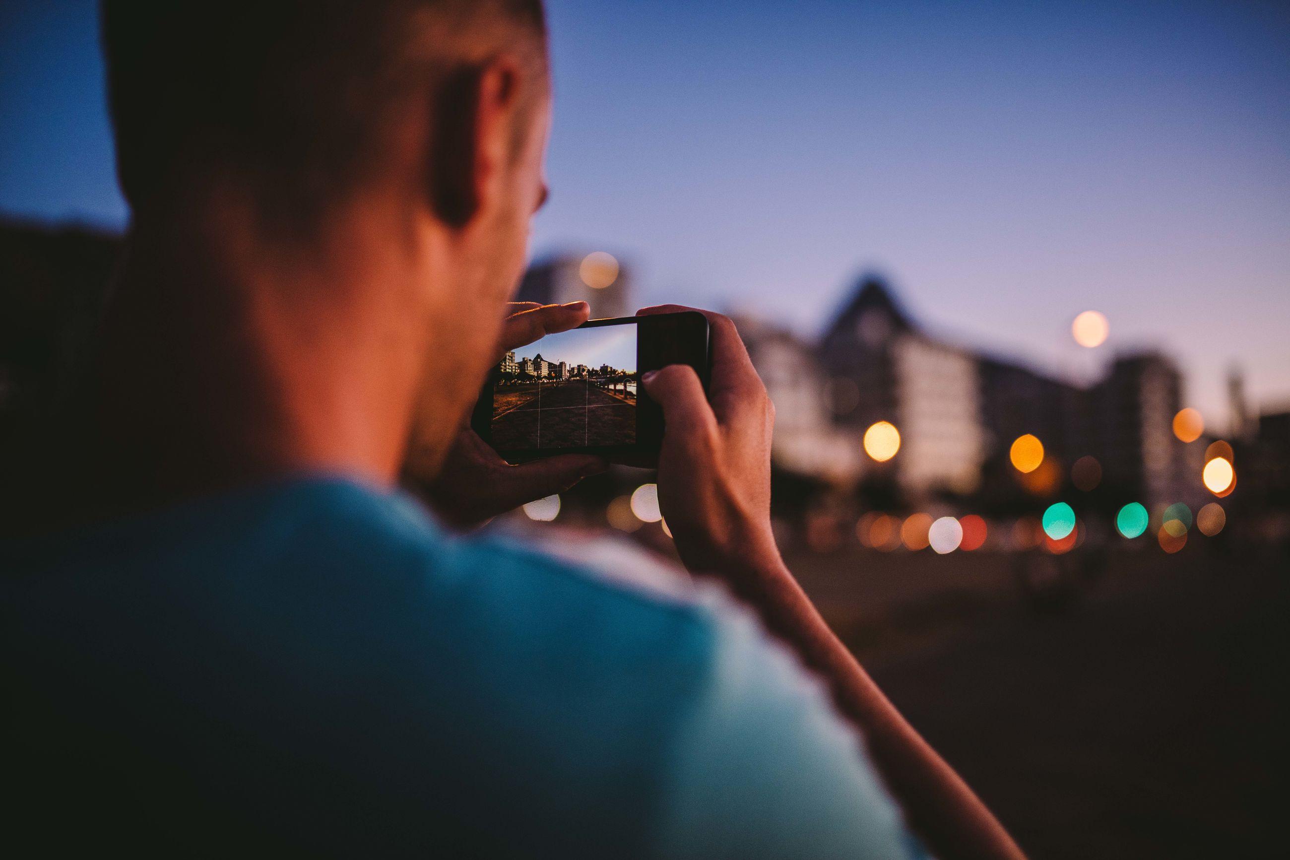 Close-up of man photographing illuminated city