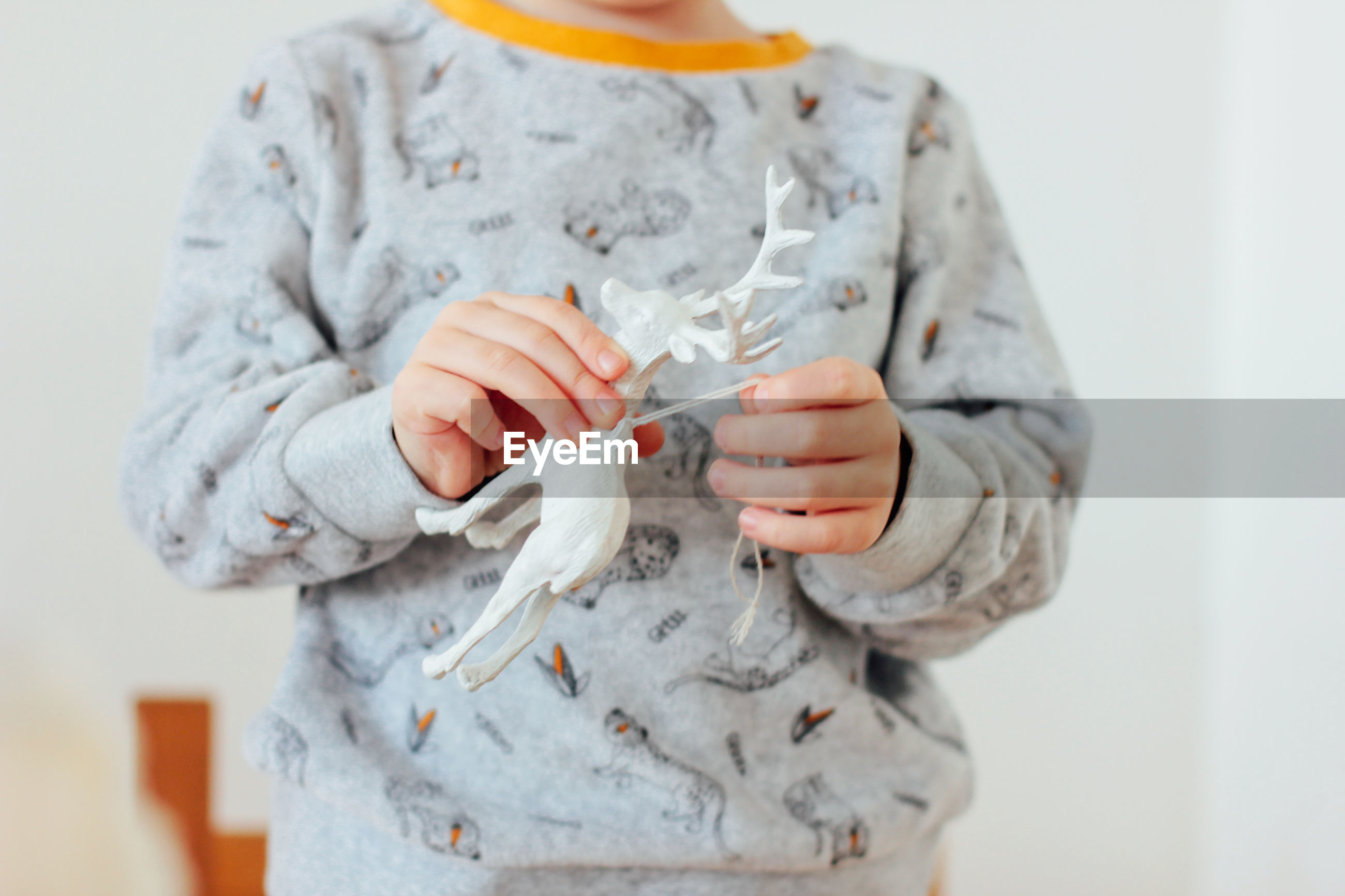 Midsection of boy holding toy at home