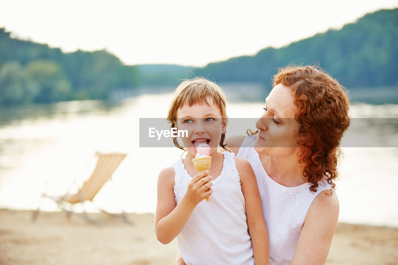 Mother looking at daughter eating ice cream