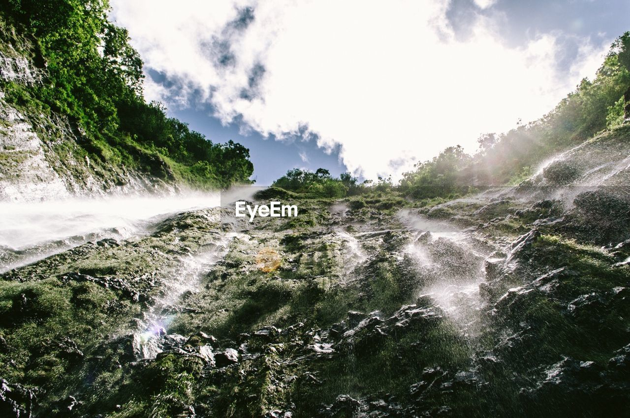 Directly below view of waterfall against sky