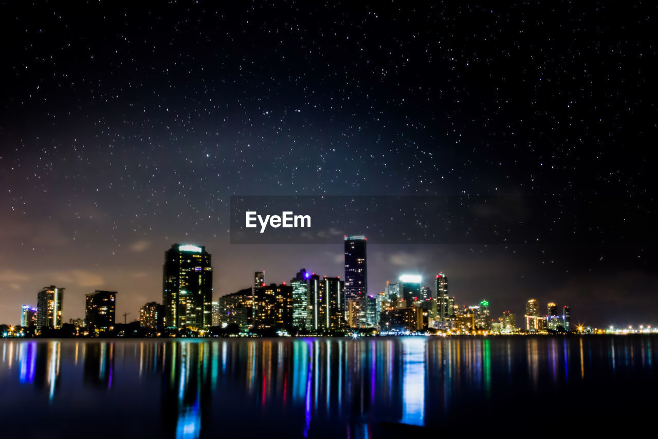night, architecture, skyscraper, illuminated, building exterior, built structure, city, modern, cityscape, development, urban skyline, no people, sky, financial district, waterfront, travel destinations, city life, growth, outdoors, tall, water