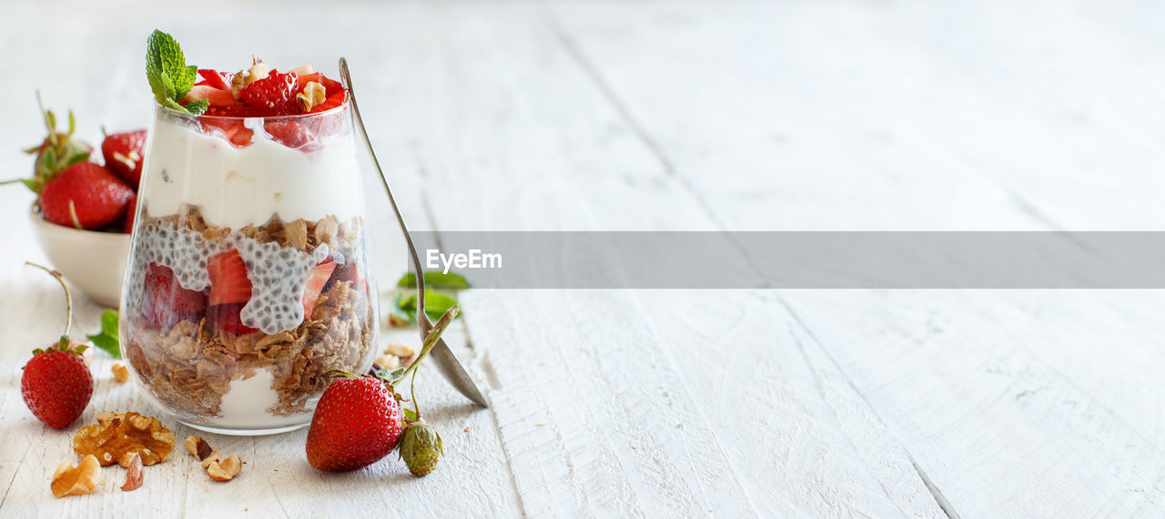 food and drink, berry fruit, fruit, food, strawberry, healthy eating, freshness, glass - material, focus on foreground, no people, container, still life, wellbeing, red, table, transparent, jar, close-up, wood - material, indoors, yogurt, glass, mint leaf - culinary, breakfast, temptation