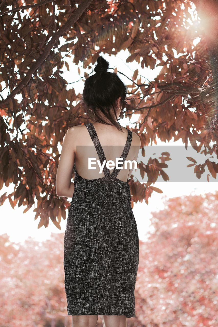 REAR VIEW OF WOMAN STANDING WITH LEAVES IN AUTUMN