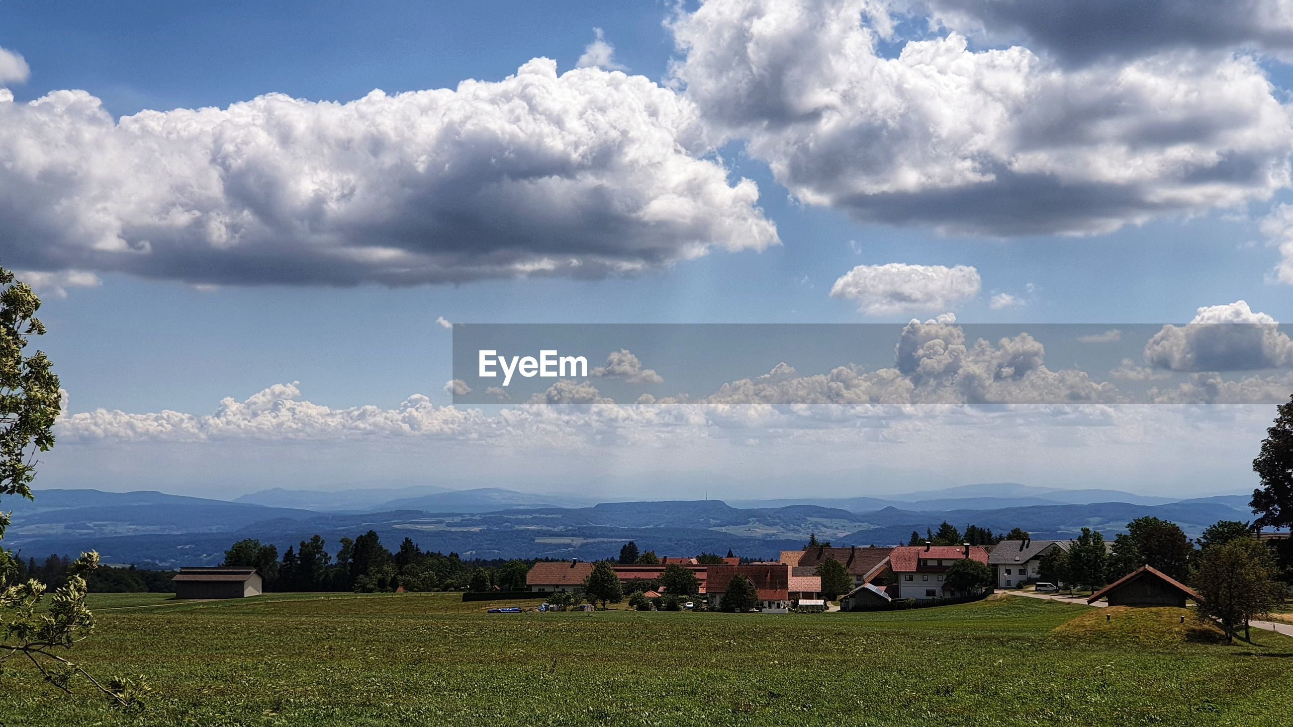 PANORAMIC VIEW OF HOUSES AND TREES AGAINST SKY