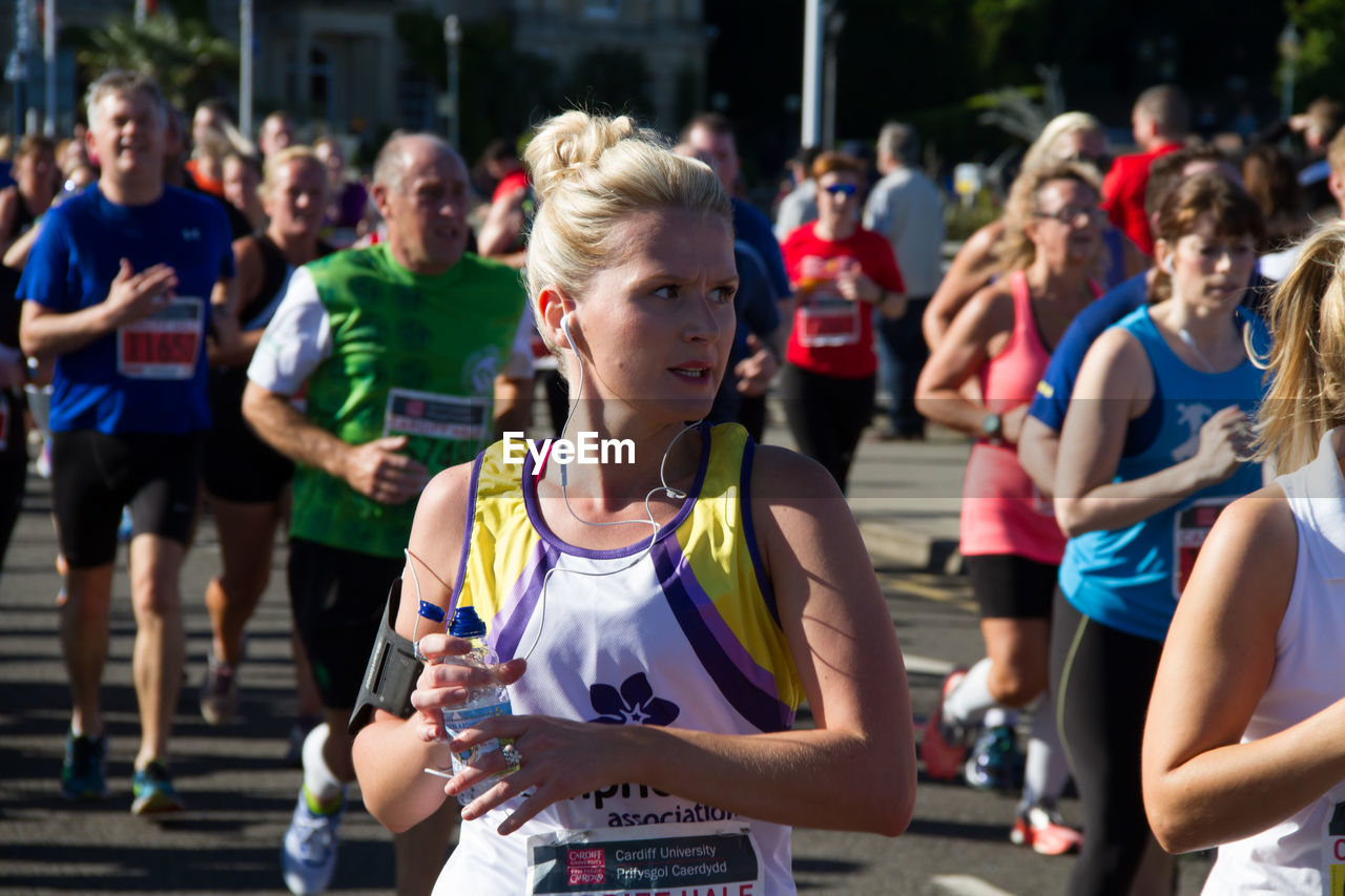 real people, focus on foreground, lifestyles, leisure activity, sports clothing, outdoors, young adult, day, sport, tank top, young women, women, large group of people, togetherness, wireless technology, men, sports race, marathon, athlete, people