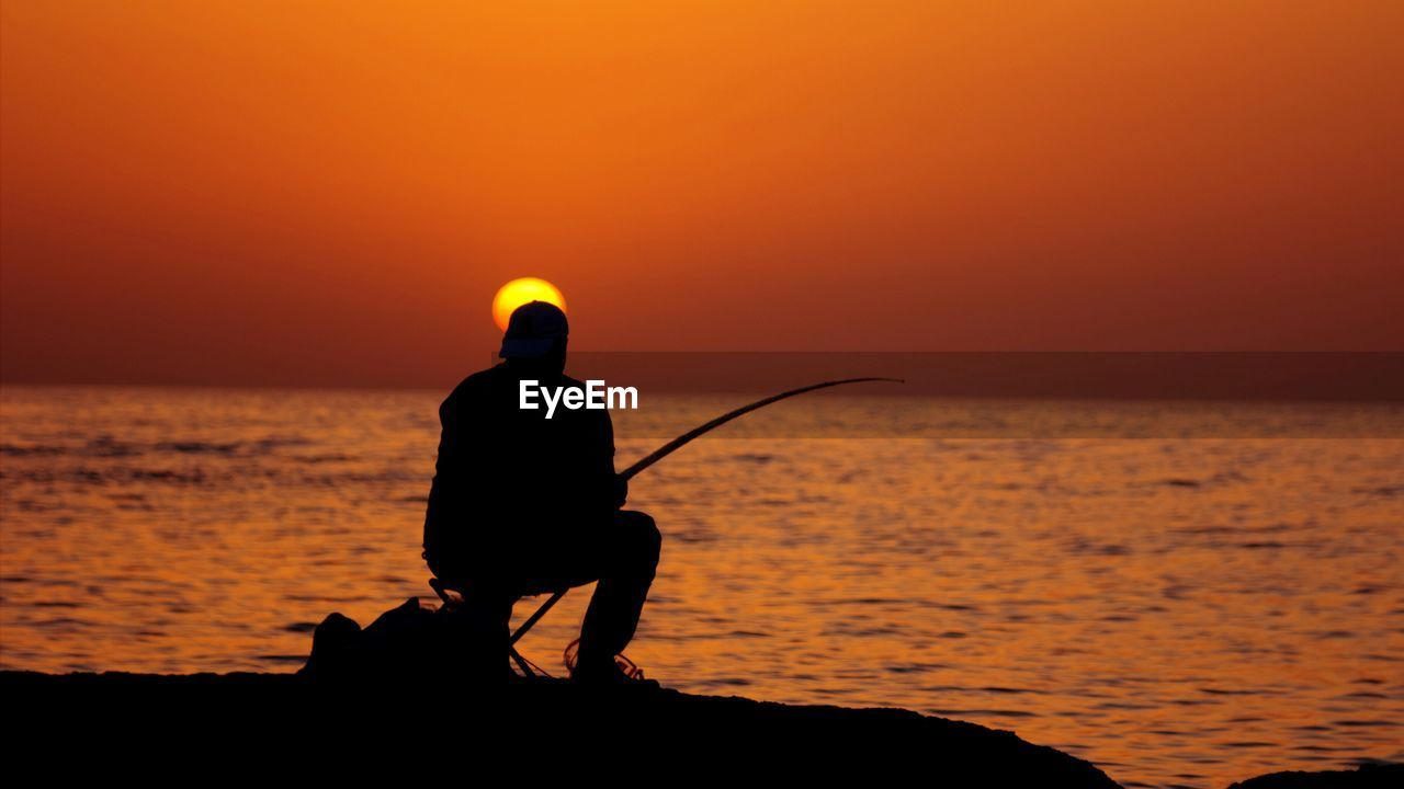 Silhouette man fishing in calm sea at sunset