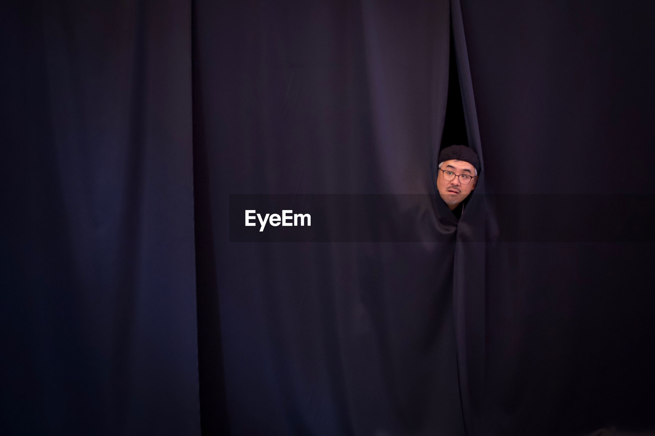 Close-up of a man looking through curtain