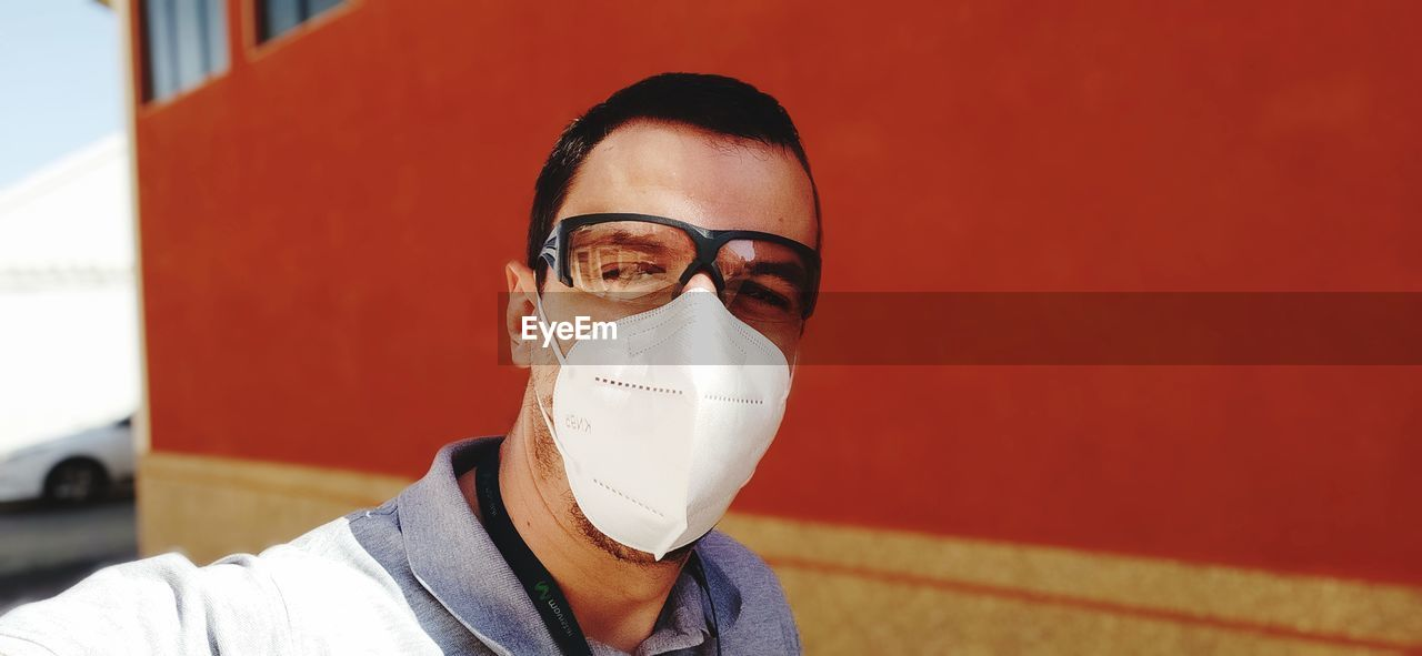 Portrait of man wearing eyewear and mask against wall