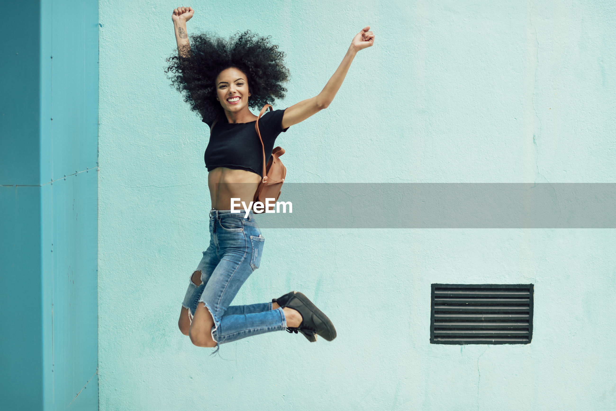 Portrait of happy young backpack woman jumping against wall