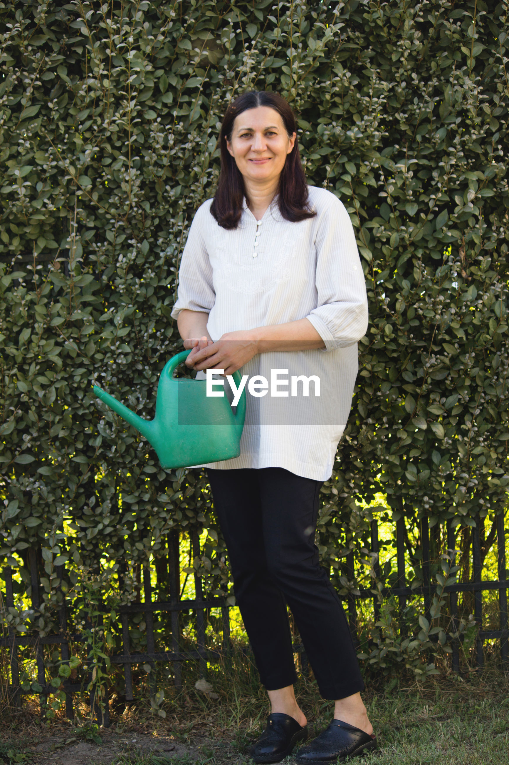Portrait of smiling woman holding watering can while standing against plants