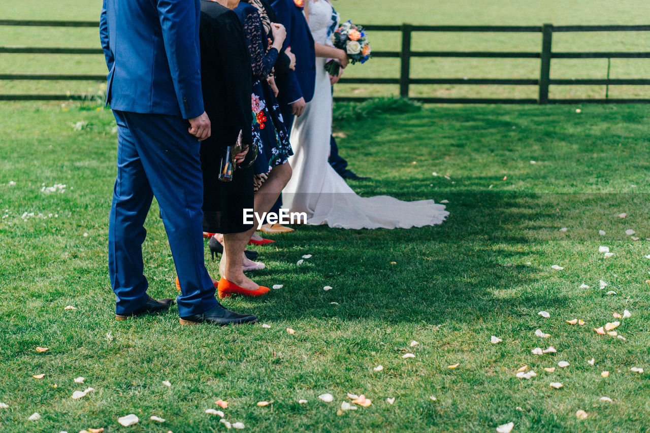 Low section of couples standing on grass