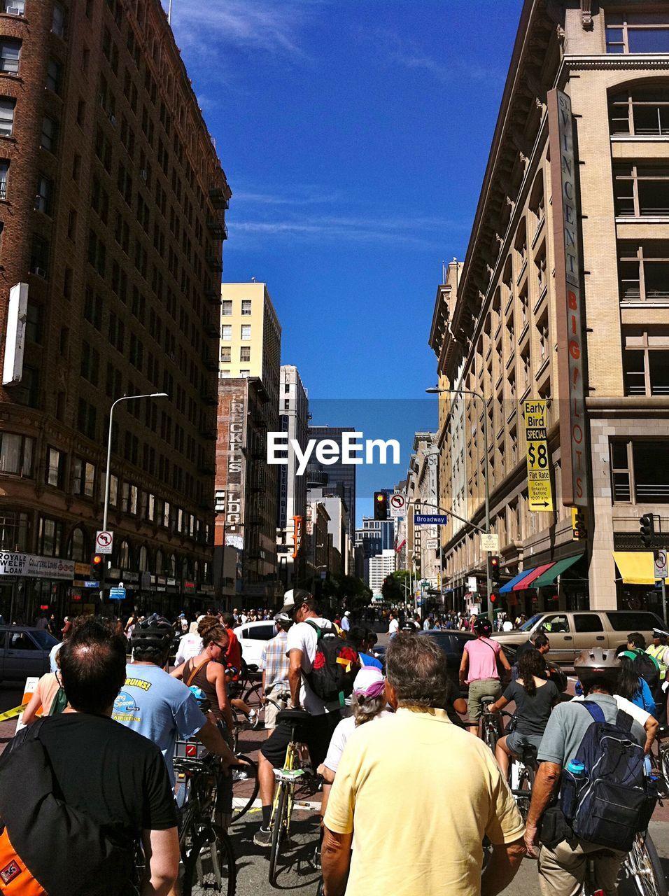 People On Street Amidst Buildings Against Blue Sky In City