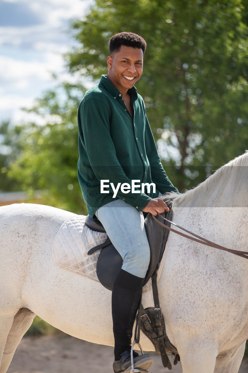 Smiling young man riding horse against tree