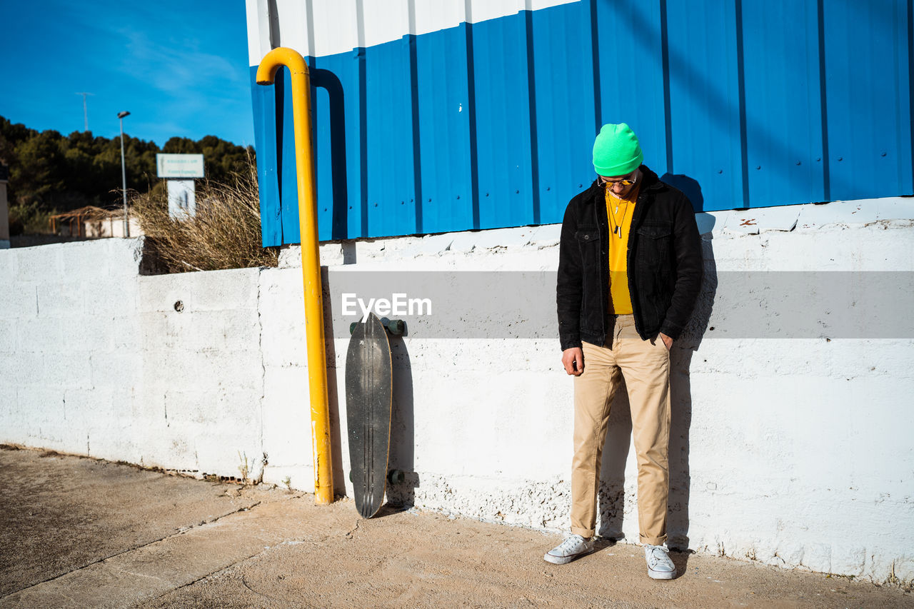 Full length of of man standing against wall outdoors