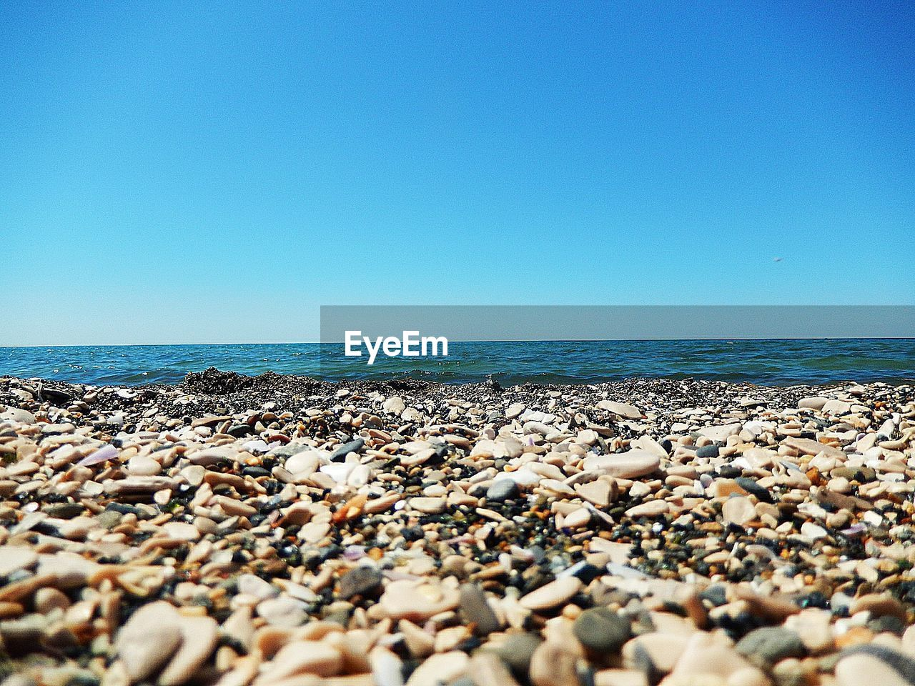 sea, horizon over water, nature, beach, water, clear sky, beauty in nature, pebble, tranquil scene, blue, scenics, shore, pebble beach, copy space, tranquility, day, outdoors, no people, sky