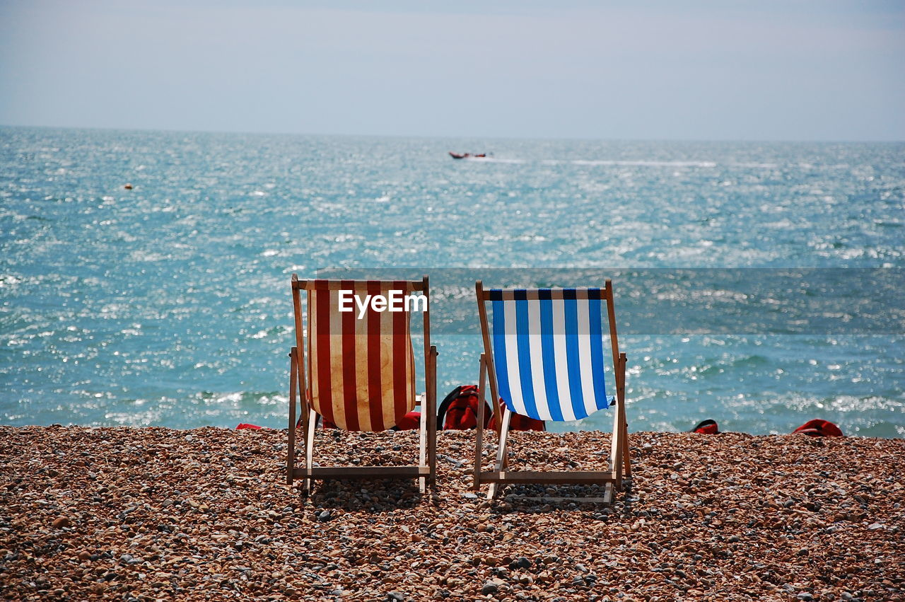 Empty folding chairs on shore against clear sky