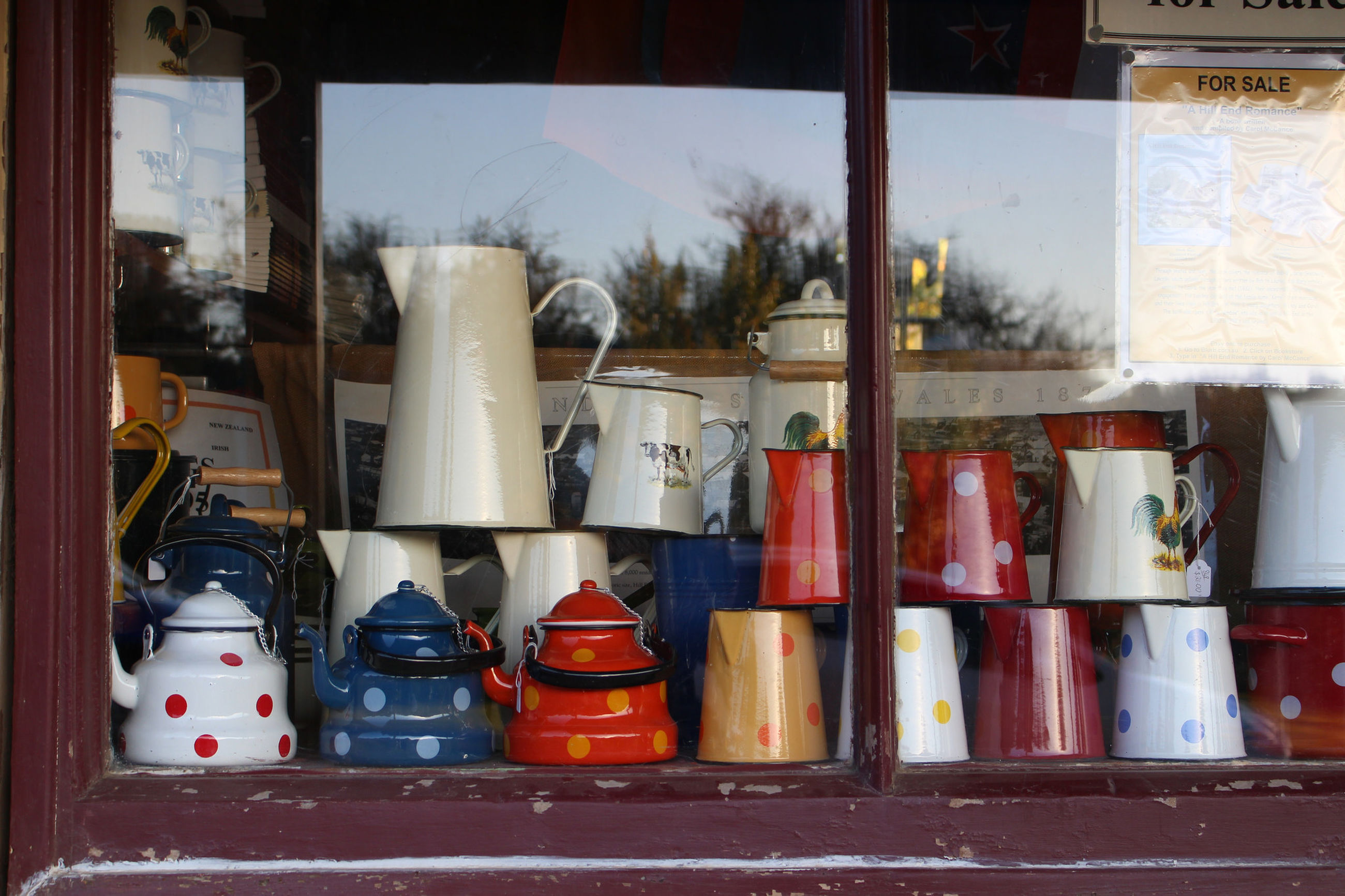 Teapots arranged on display widow for sale in shop