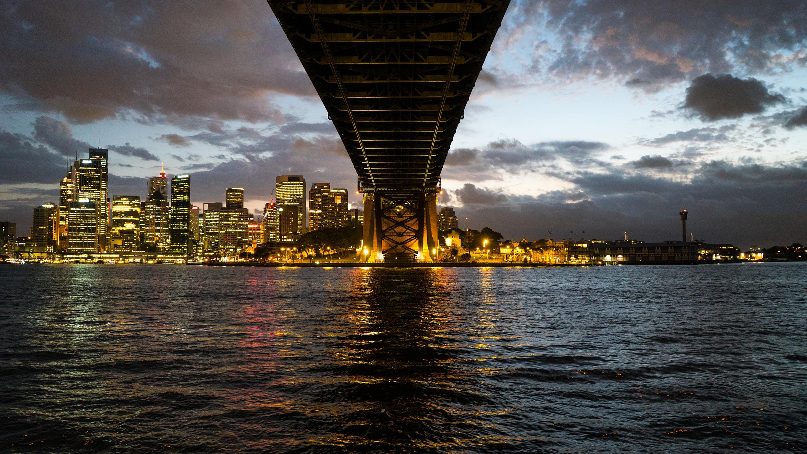 Bridge over river leading towards illuminated city against sky at sunset